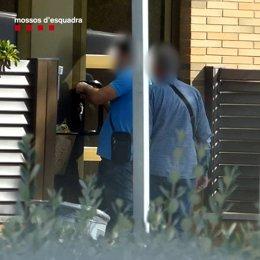 Els lladres arrestats forçant el pany de la porta d'accés d'un dels habitatges del Vallès (Vertical).