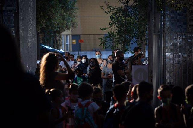 Pares i alumnes esperen a les portes d'una escola durant el primer dia del curs escolar 2020-2021, a Barcelona, Catalunya (Espanya), 14 de setembre del 2020.