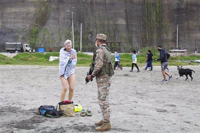 Un soldado peruano pide a una mujer abandonar la playa, que aún permanece cerrada por la pandemia.