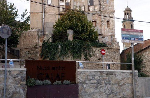 Pla general d'ampolles penjades al costat del cartell d'entrada al nucli antic de Calaf. Imatge del 10 d'octubre del 2020.