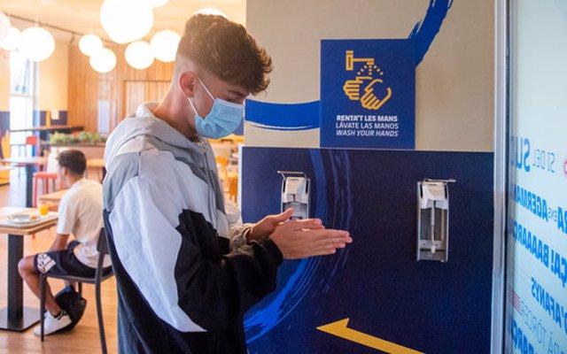 Pla mitjà d'un jugador de la Masia del Barça netejant-se les mans en un espai habilitat del centre. Imatge del 12 d'octubre del 2020 (horitzontal)