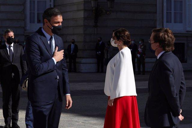 El presidente del Gobierno, Pedro Sánchez, saluda a la presidenta de la Comunidad de Madrid, Isabel Díaz Ayuso y al alcalde de la capital, José Luis Martínez-Almeida, su llegada al Palacio Real