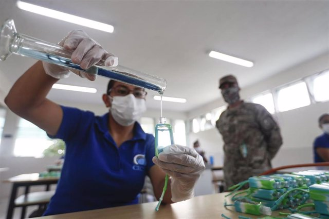 Una mujer llena botellas con desinfectante en Perú para luchar contra el coronavirus.