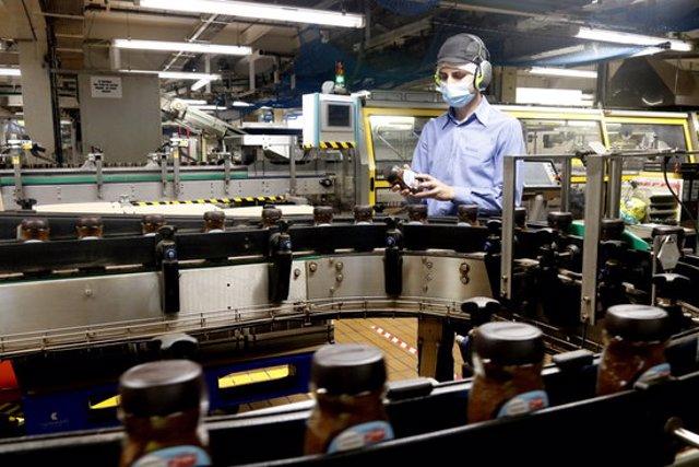 Un treballador inspecciona un pot de Nescafé al costat d'una de les línies de producció de la fàbrica de Girona. Pla general. Imatge publicada el 13 d'octubre del 2020 (Horitzontal)