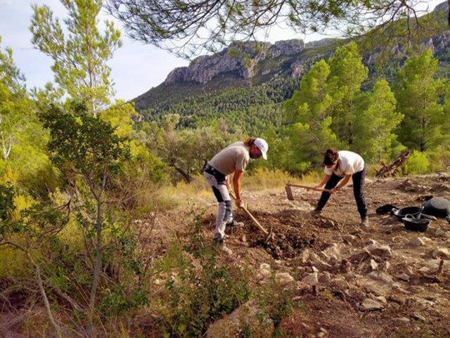 Pla general de dos arqueòlegs treballant al jaciment. Foto del 13 d'octubre del 2020 (Horitzontal).