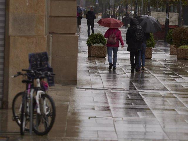 Transeúntes pasean por una calle de Pamplona protegidos con mascarilla debido a la crisis sanitaria del Covid-19, en Pamplona