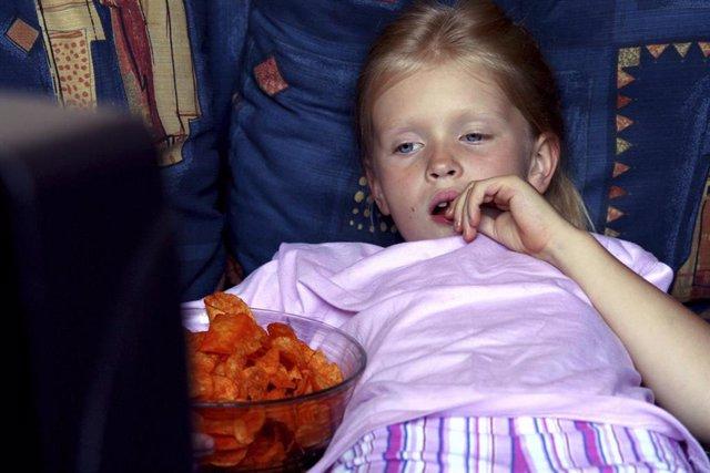 Niña frente a la televisión comiendo patatas
