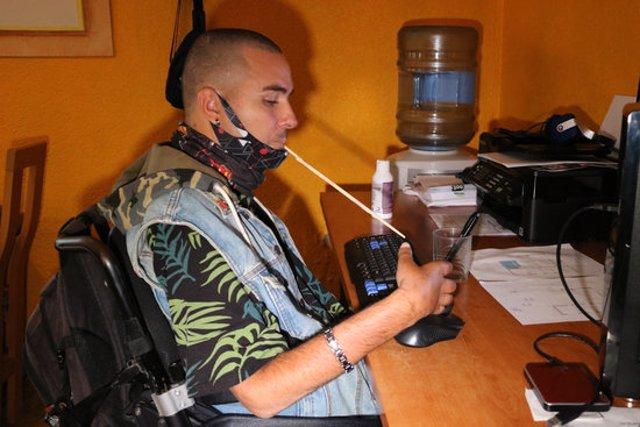 Pla mitjà de Miguel Bejarano, un veí de Calafell amb una incapacitat del 96% per un accident laboral ocorregut el 2006, en el moment que escriu amb l'ajuda d'un pal. Imatge de l'octubre del 2020 (horitzontal)