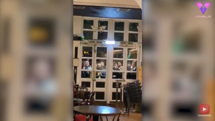 Aficionados escoceses terminan de ver un partido de fútbol a través del cristal del bar que acaba de desalojarlos