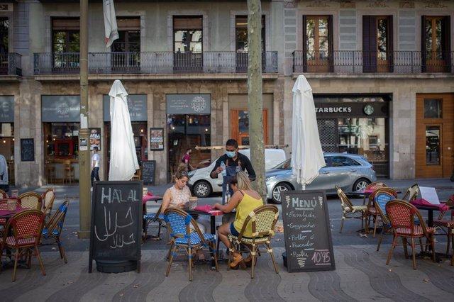 Dues dones mengen a la terrassa d'un bar a Barcelona, Catalunya (Espanya), 14 d'octubre del 2020.