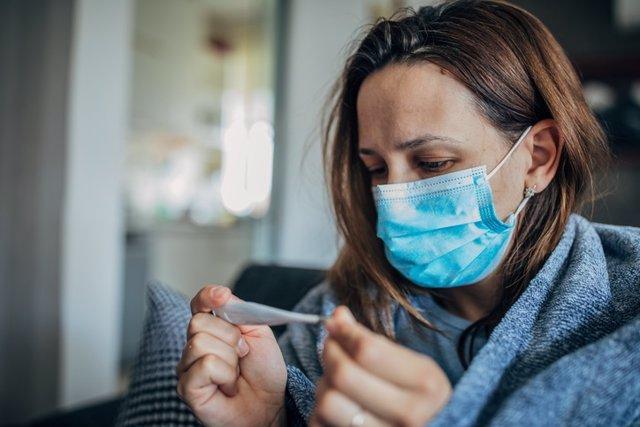 Mujer enferma mirando el termómetro. Covid-19, coronavirus, gripe.