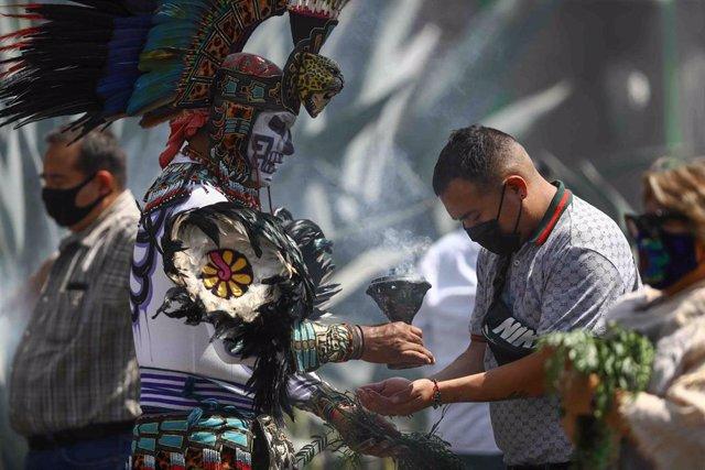 Un grupo de personas se someten a una 'limpia' de espíritu de los llamados concheros  en la céntrica plaza de El Zócalo, en Ciudad de México.