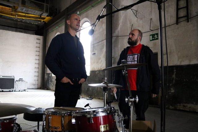 Marc Sempere i El Niño de Elche conversen al davant d'una bateria a la fàbrica de l'Anònima de Manresa. Imatge publicada el 15 d'octubre de 2020. (Horitzontal)