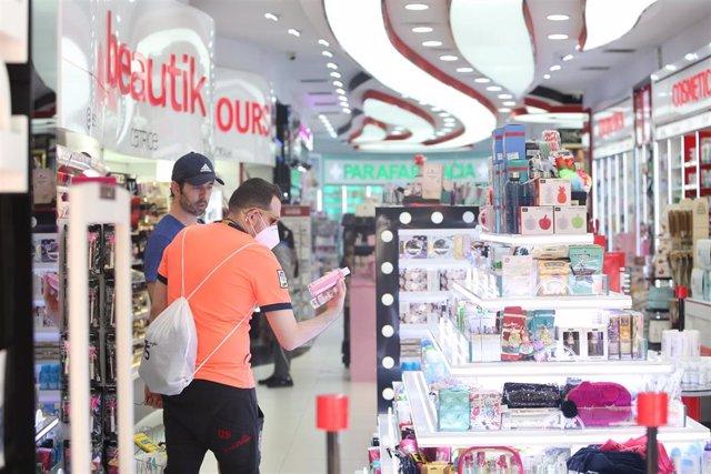 Dos clientes miran productos en una tienda de cosméticos