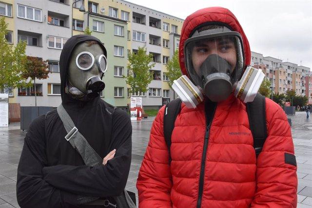 Dos personas con máscaras de gas en Polonia después de que las autoridades hayan obligado a usar mascarilla por la pandemia