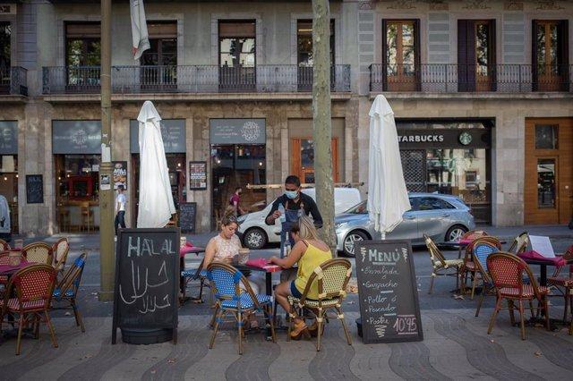 Dos mujeres comen en la terraza de un bar en Barcelona (Archivo)