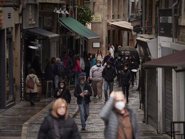 Transeúntes pasean por una calle de Pamplona protegidos con mascarilla debido a la crisis sanitaria del Covid-19, en Pamplona, Navarra, (España), a 11 de octubre de 2020. El Gobierno de Navarra aprobará una orden foral con nuevas medidas restrictivas para