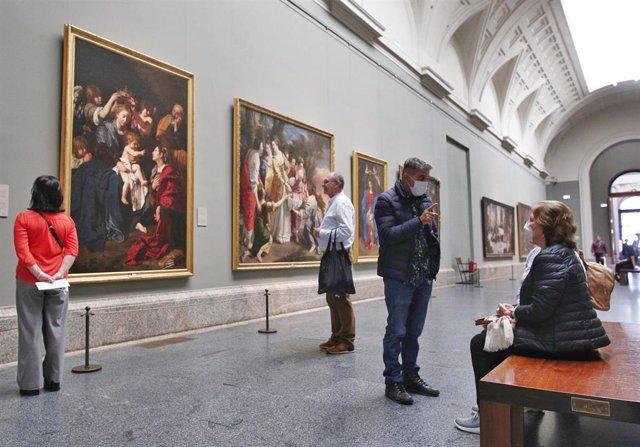 Dos personas con mascarillas en la Galería Central del Museo Nacional del Prado el mismo día en el que el Museo, junto con el Reina Sofía y el Thyssen, cierra como medida de contención frente a la crisis del coronavirus, en Madrid (España) a 11 de marzo d
