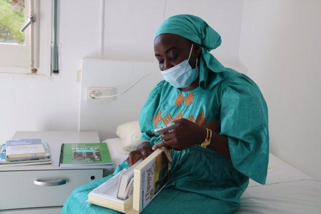 Sina Ndiaye, usuària del Centre Residencial d'Inclusió La Llavor per a dones sense llar, a la seva habitació fullejant un llibre. 15 d'octubre del 2020. (Horitzontal)