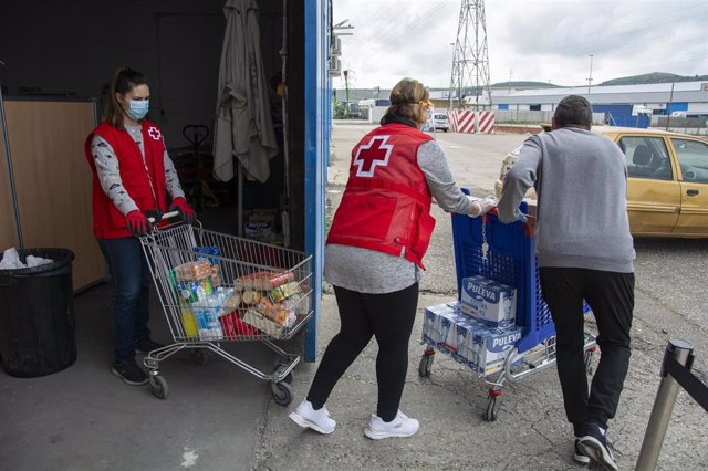 Voluntarios de Cruz Roja con carros de alimentos