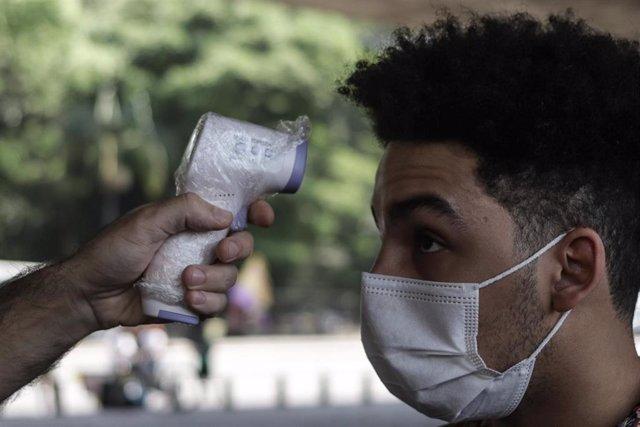Una joven se somete una prueba de temperatura antes de ingresar en un espacio público de Sao Paulo, Brasil.