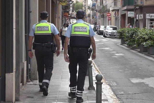 Dos agents de la Guàrdia Urbana de Figueres patrullant pel centre de la ciutat, en una imatge d'arxiu. (Horitzontal)