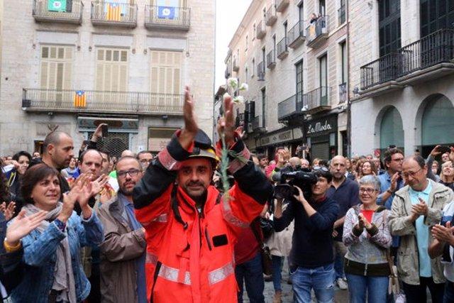 Pla mig d'un bomber tornant els aplaudiments a la Plaça del Vi de Girona el 2 d'octubre del 2017, durant la concentració que es va fer (Horitzontal)
