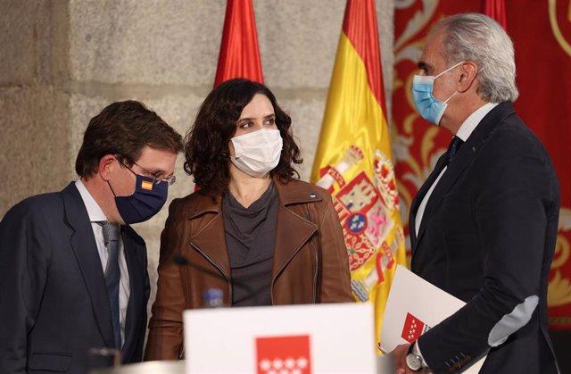 La presidenta de la Comunidad de Madrid, Isabel Díaz Ayuso; el alcalde de Madrid, José Luis Martínez-Almeida; y el consejero de Sanidad de la Comunidad de Madrid, Enrique Ruiz Escudero, en la sede del Gobierno regional, en Madrid, a 13 de octubre