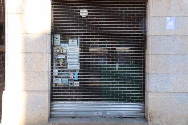 Pla obert de dues persones esmorzant en un banc després de comprar un entrepà i un cafè per emportar al carrer d'Hortes de Girona el 16 d'octubre de 2020 (Horitzontal)