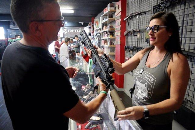 Un hombre observa un fusil en una tienda de armas en Florida