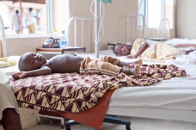Dos niños descansan en una unidad pediátrica en África