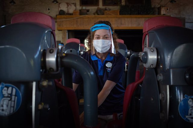 Una treballadora de PortAventura World protegida amb mascareta i pantalla.