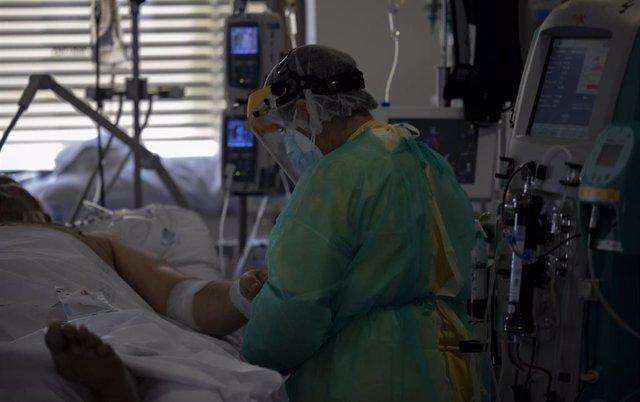 Un sanitario atiende a un paciente en la Unidad de Cuidados Intensivos (UCI) dedicada a enfermos de coronavirus del Hospital Universitario Ramón y Cajal