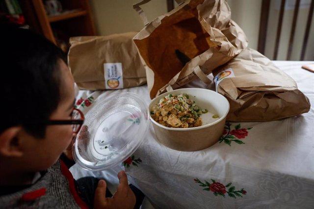 Un niño durante la comida en su casa del barrio madrileño de Carabanchel abre la tapa de un plato del menú de la ONG del chef José Andrés, en Madrid (España) a 14 de abril de 2020.