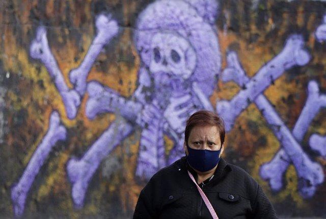 Una mujer llevando mascarilla frente a un mural en recuerdo de los muertos por coronavirus en México.