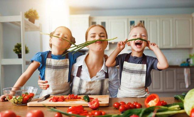 Madre cocinando con sus dos hijos de forma divertida.