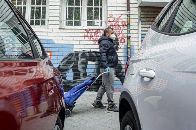Vecinos realizan una cola para recoger bolsas de la Asociación de Vecinos Parque Aluche. En Aluche, Madrid, (España), a 16 de mayo de 2020.