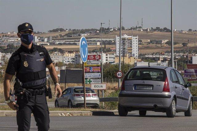 n policía nacional en un control a la entrada del pueblo sevillano de Écija, en el primer día en el que la Junta de Andalucía resolvió, mediante un boletín oficial (BOJA) extraordinario, que la restricción durante diez días naturales de las entradas y sal