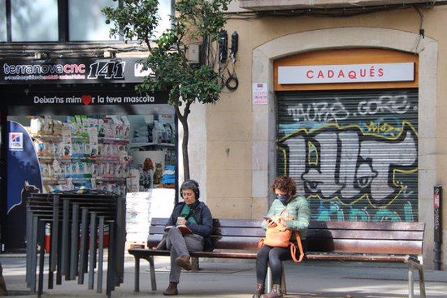 Pla obert de dues dones assegudes en un banc a la plaça de la Vila de Gràcia, davant un resturant tancat per les noves restriccions. Imatge del 17 d'octubre de 2020. (Horitzontal)