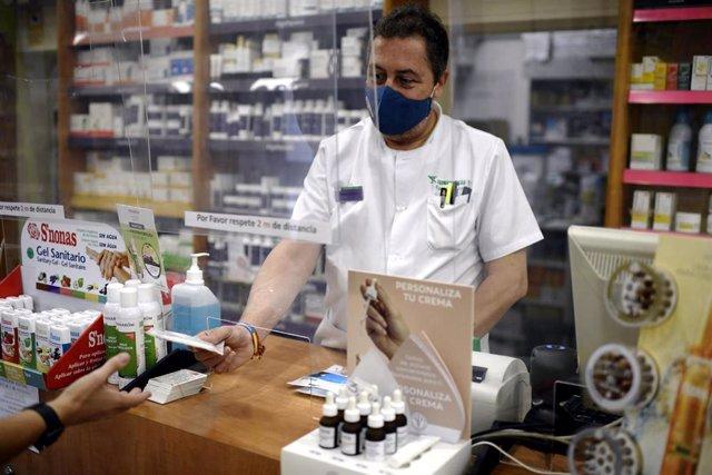 Un farmacéutico entrega a un cliente una de las mascarillas KN95 que ha recibido en su farmacia