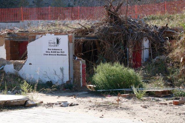 Runes arran de riu a l'Espluga de Francolí on destaca el missatge dels propietaris del celler derruït, comunicant la nova ubicació.  Imatge del 15 octubre del 2020. (Horitzontal)