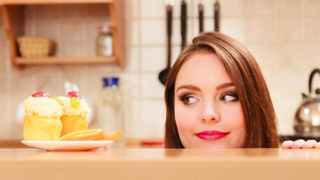 Mujer mirando un pastel con hambre.