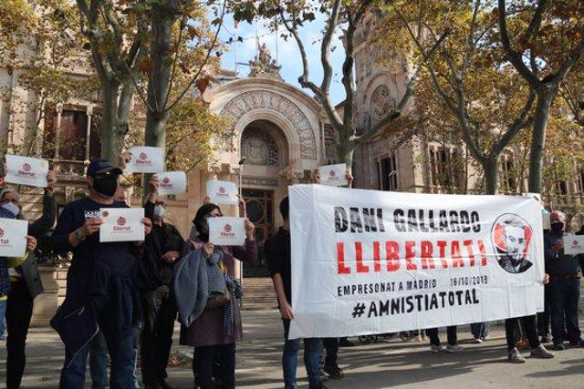 Pla obert de diversos manifestants davant el TSJC mostrant una pancarta en suport a Dani Gallardo, detingut a Madrid per les protestes de la sentència de l'1-O. Imatge del 18 d'octubre de 2020. (Horitzontal)