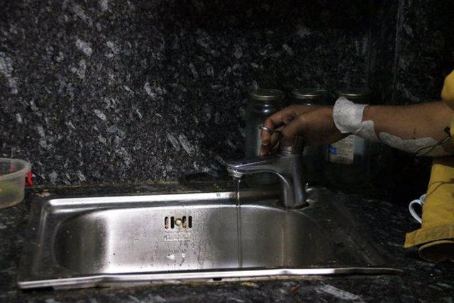 Pla detall d'una aixeta amb aigua d'un dels pisos del bloc de pisos ocupat al carrer Ignasi Balcells de Manresa. Imatge del 19 d'octubre del 2020. (Horitzontal)