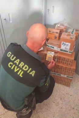 Un agent de la Guàrdia Civil, en un operatiu en el qual es van incautar més de 15.000 piles de marques falsificades al Baix Ebre i a la Ribera d'Ebre. Imatge publicada el 19 d'octubre del 2020. (Vertical)