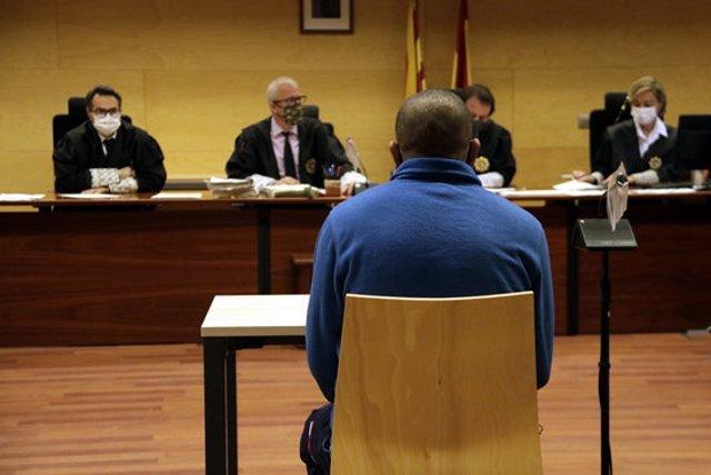 D'esquenes, l'acusat de violar i apunyalar l'exparella a Figueres. Foto del judici a l'Audiència de Girona el 19 d'octubre del 2020 (horitzontal)
