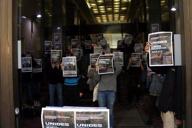Universitaris del Sindicat d'Estudiants dels Països Catalans (SEPC) i de les assemblees de facultat mostren cartells de la vaga del 21 d'octubre a dins de l'entrada del Departament d'Empresa, que han ocupat durant una hora. 19 octubre 2020. (Horitzontal)