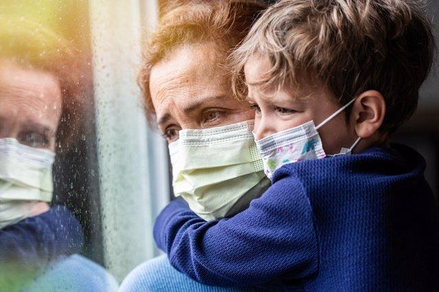 Covid-19, mujer y niño con mascarilla mirando por la ventana.