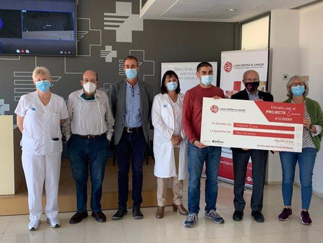 Foto de família dels representants de la Lliga Contra el Càncer i del projecte Emma en la presentació de l'acord de col·laboració per dotar amb 30.000 euros el finançament de la recerca. Imatge del 19 d'octubre del 2020 (horitzontal)