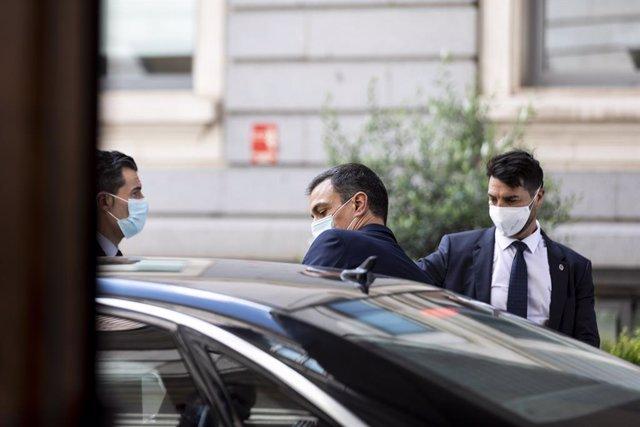 El presidente del Gobierno, Pedro Sánchez, con mascarilla, accede a su coche tras una sesión de control al Ejecutivo en el Congreso